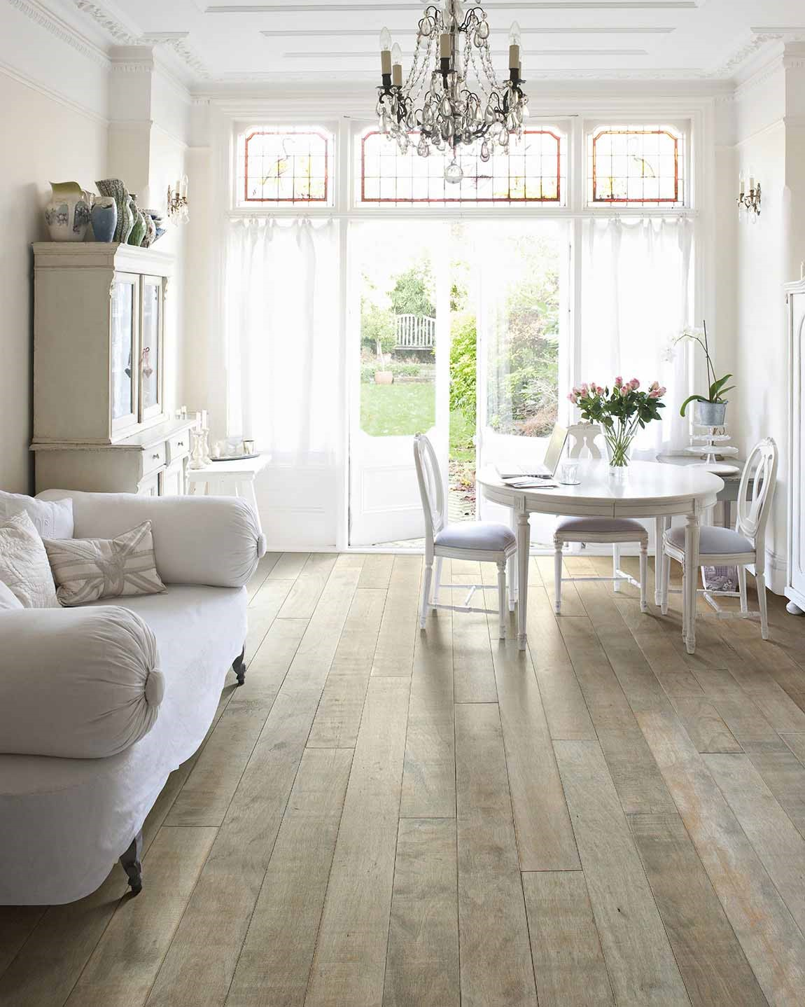 bright living room with white furniture and light hardwood flooring